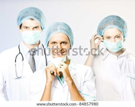 happy doctors with surgery masks - stock photo