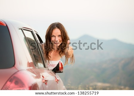 Happy driver woman showing thumb up sign against mountains background. Summer vacations concept - stock photo