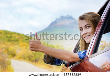 Happy driver woman shows thumb up against mountains background. Travel vacations concept  - stock photo