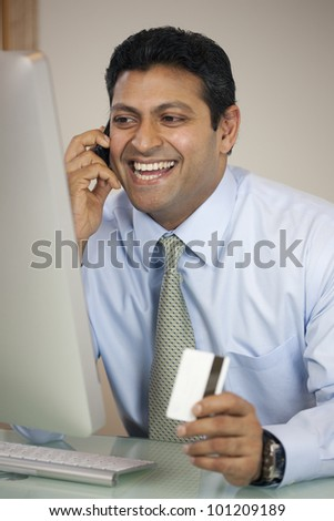 Happy East Indian businessman on the phone with credit card at his computer - stock photo