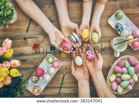 Happy easter! A mother, father and their daughter painting Easter eggs. Happy family preparing for Easter.  - stock photo