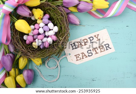 Happy Easter background with painted Easter eggs in birds nest, and yellow and purple silk tulips and ribbon on vintage style rustic distressed aqua blue wood table, with greeting tag. - stock photo
