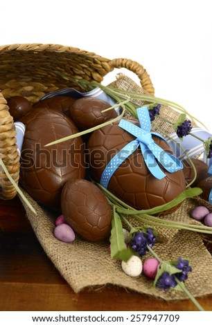 Happy Easter basket hamper of chocolate Easter Eggs and flower on dark wood table. - stock photo
