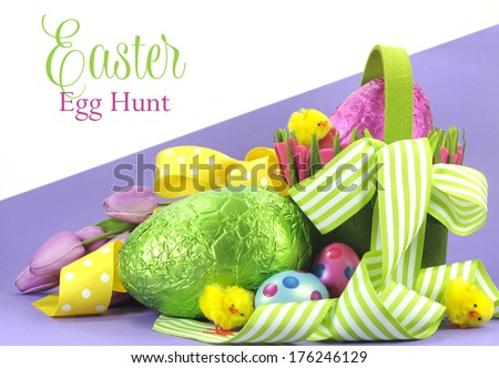 Happy Easter bright color Easter egg hunt theme with yellow, green ribbons and basket of eggs and chicks with sample greeting or copy space for your text here. - stock photo