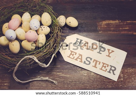Happy Easter candy easter eggs in birds nest on dark vintage recycled wood background with Happy Easter gift tag sign message greeting, with applied retro style filters.
