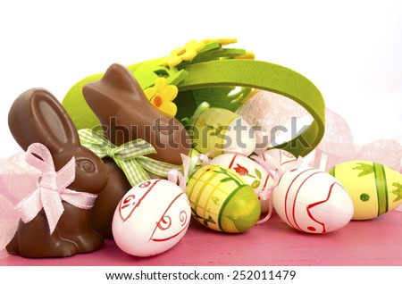 Happy Easter chocolate bunny rabbits with basket of pink, white and green eggs on vintage pink wood background. - stock photo