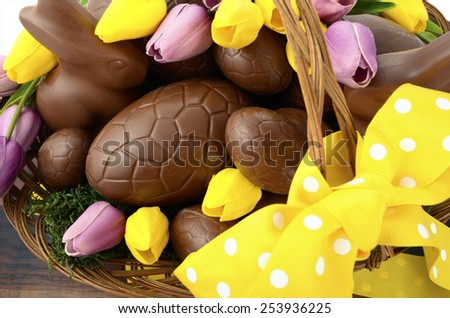 Happy Easter chocolate hamper of eggs and bunny rabbits in large basket with yellow and pink purple silk tulip flowers on dark wood table, overhead. - stock photo