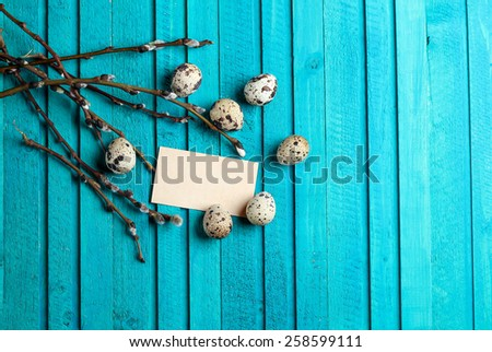 Happy easter concept. Quail eggs and willow branch on a wooden background. Selective focus. Copy space note - stock photo