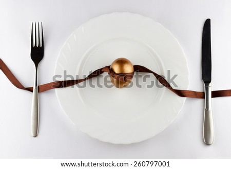 Happy Easter concept. Top view of golden egg with ribbon in the white plate with silver fork and knife  - stock photo