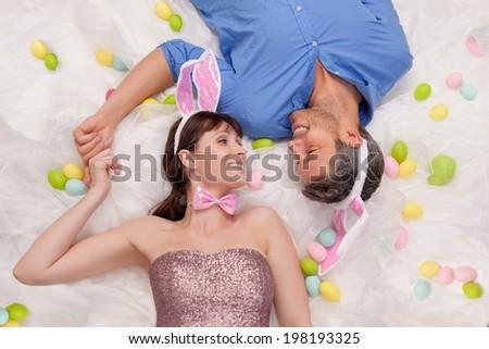 happy easter couple lying smiling - stock photo
