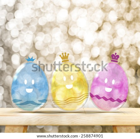 Happy Easter Day : Three Colorful Glitter transparency glass egg with smile face on wood table with golden sparkling background, Leave copy space to adding your text - stock photo