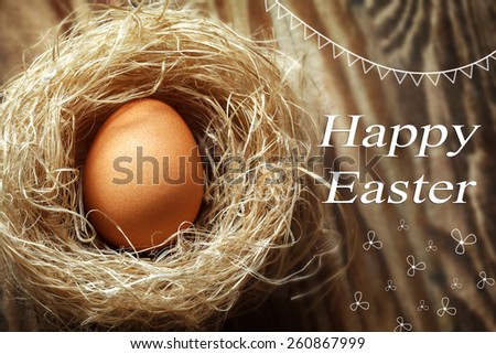 Happy easter egg in hay nest on wooden background - stock photo