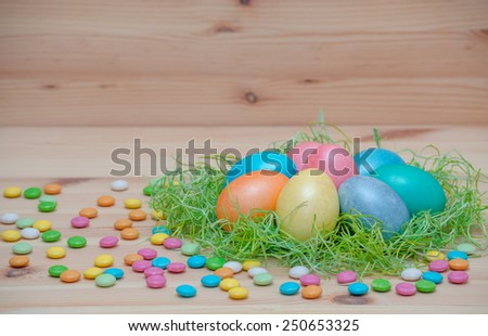 happy easter eggs pastel colored in a nest on the vintage wooden background - stock photo