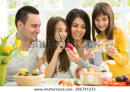 Happy Easter family choosing  a thumbnail image for eggs - stock photo