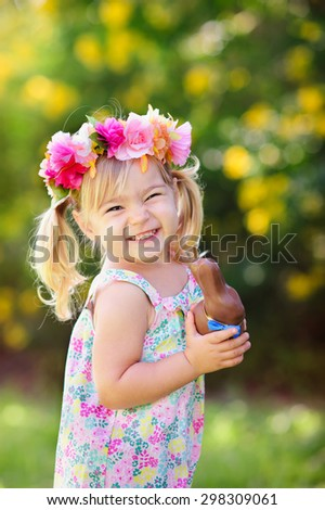 happy easter girl eat chocolate bunny at meadow background - stock photo