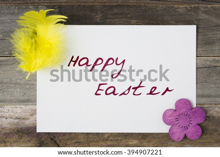 Happy Easter greeting card surrounded by feather and wooden Easter flower.