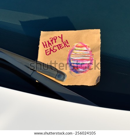 Happy Easter - Message under a windshield wiper with hand written text and a hand drawn easter egg  - stock photo