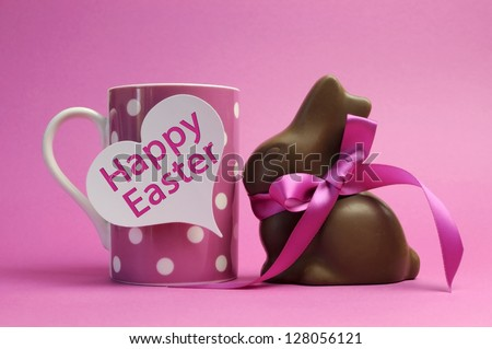 Happy Easter pink polka dot coffee or tea mug with white heart shape gift tag sign and chocolate bunny with pink ribbon, with Happy Easter message. - stock photo