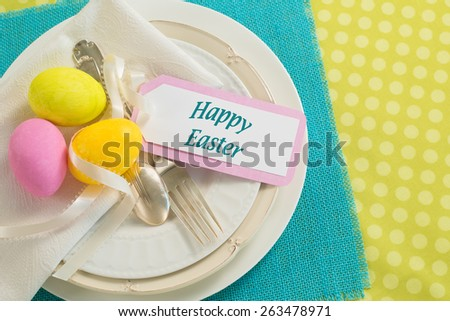 Happy Easter Place Setting with 3 Dyed Eggs on White Plates with Note Card and Cyan and Green Cloth Mats and Background room or space for copy, text, your words.  Horizontal above view, looking down. - stock photo