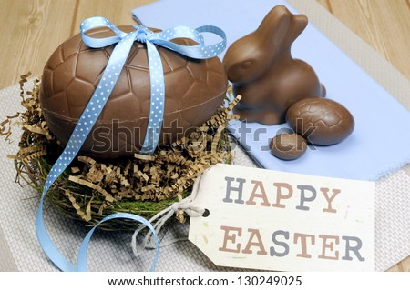 Happy Easter still life with chocolate eggs, bunny and gift tag on wood table. - stock photo