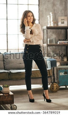 Happy effortlessly stylish brunet woman staying in loft living room and and talking smartphone - stock photo