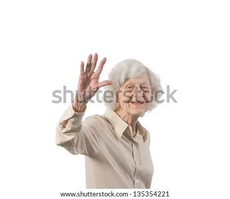 Happy elder lady waving. Isolated against white background with copy space. - stock photo