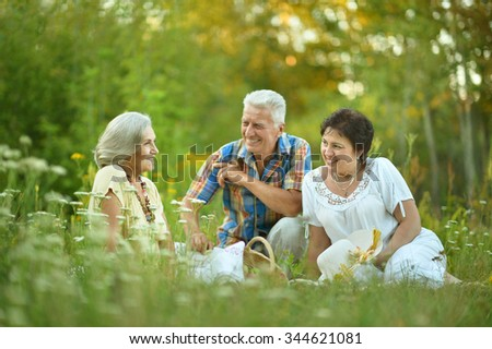 Happy elder people resting on grass at nature - stock photo