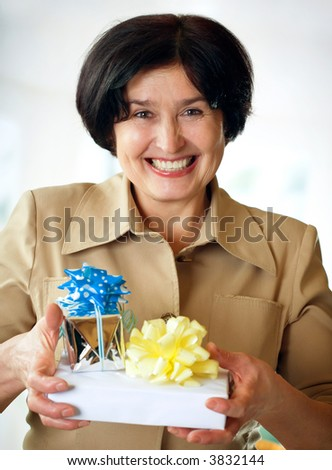 Happy elderly attractive woman with giftboxes, smiling