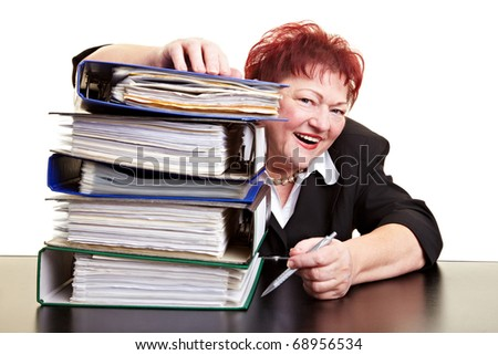 Happy elderly business woman smiling behind files