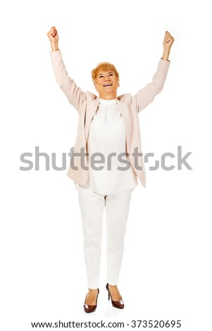 Happy elderly business woman with arms up - stock photo
