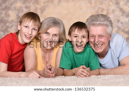 Happy elderly couple and their grandchildren are lying on the floor