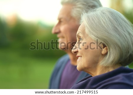Happy elderly couple at nature on leaves and sunset background - stock photo
