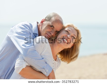 Happy elderly couple at sea vacation smiling and hug together