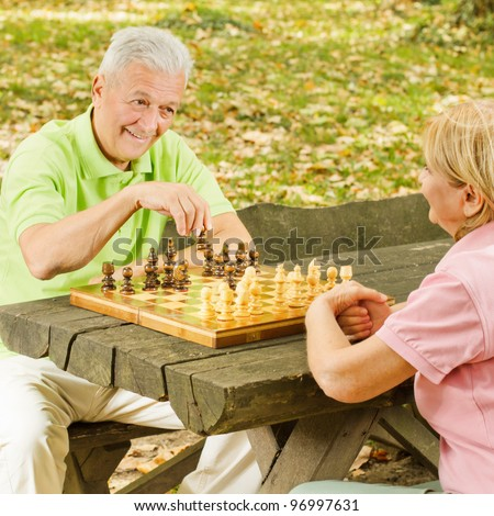 Happy elderly couple has fun playing chess in the park. - stock photo