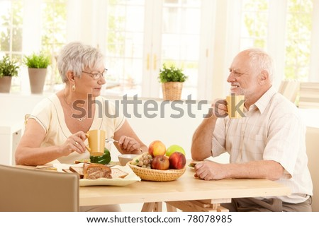 Happy elderly couple having breakfast together at home, smiling, having coffee.?