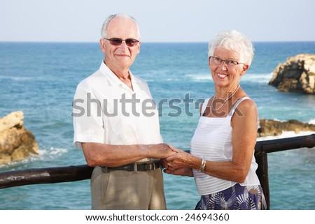 happy elderly couple holding hands - bright lifestyle portrait - stock photo
