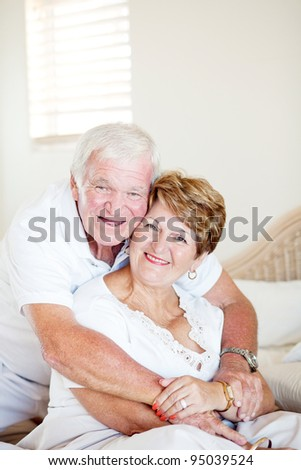happy elderly couple hugging in bedroom - stock photo