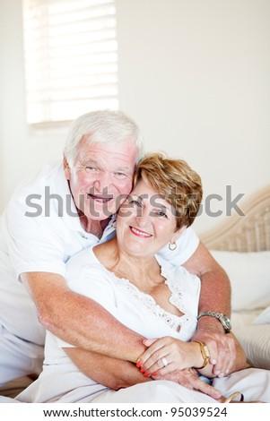 happy elderly couple hugging in bedroom - stock photo