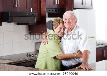 happy elderly couple hugging in home kitchen - stock photo