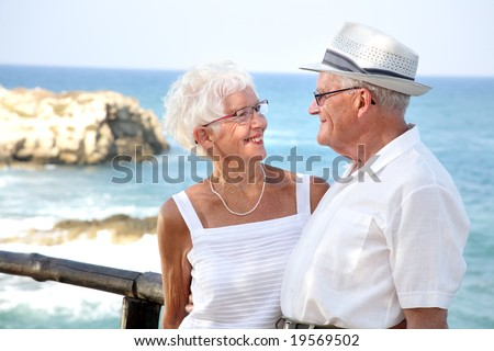 happy elderly couple in love, looking in each other's eyes - stock photo