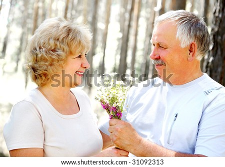 happy elderly couple in the summer forest
