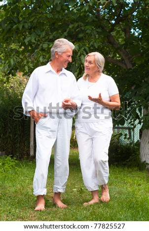 happy elderly couple in white clothes at nature