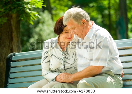 Happy elderly couple listening music in headset or praying together, outdoors - stock photo