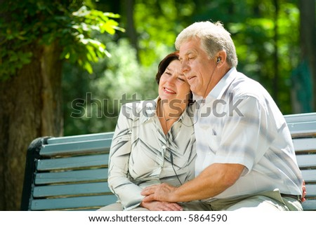 Happy elderly couple listening music in headset together, outdoors - stock photo