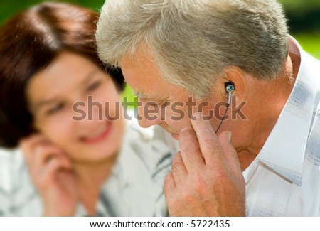 Happy elderly couple listening music in headset together, outdoors. Focus on man. - stock photo