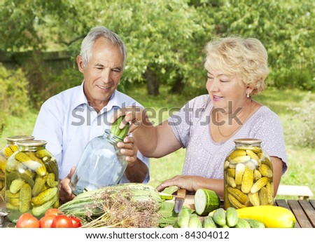 Happy elderly couple making home made pickles - stock photo