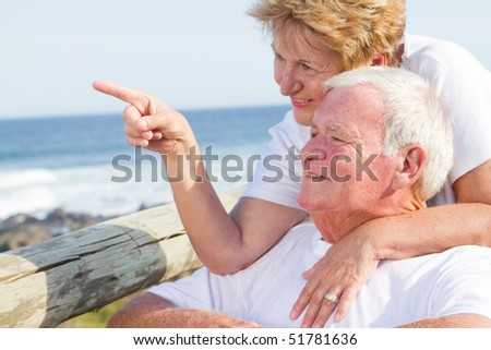 happy elderly couple on beach - stock photo