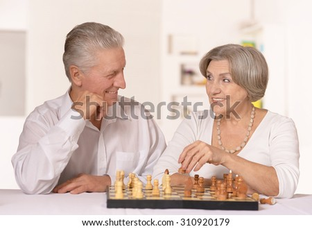 Happy elderly couple playing chess at home - stock photo