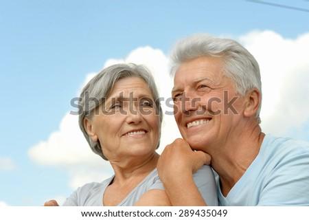 Happy elderly couple posing against the sky - stock photo