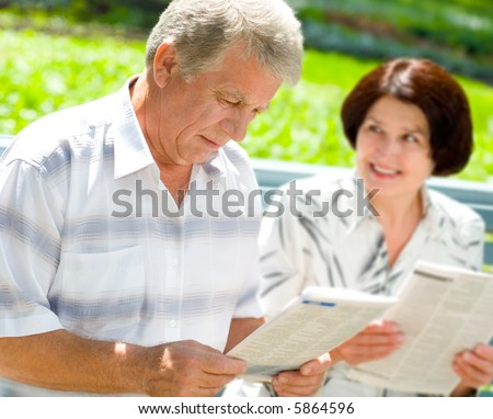 Happy elderly couple reading together outdoors. Focus on man. - stock photo